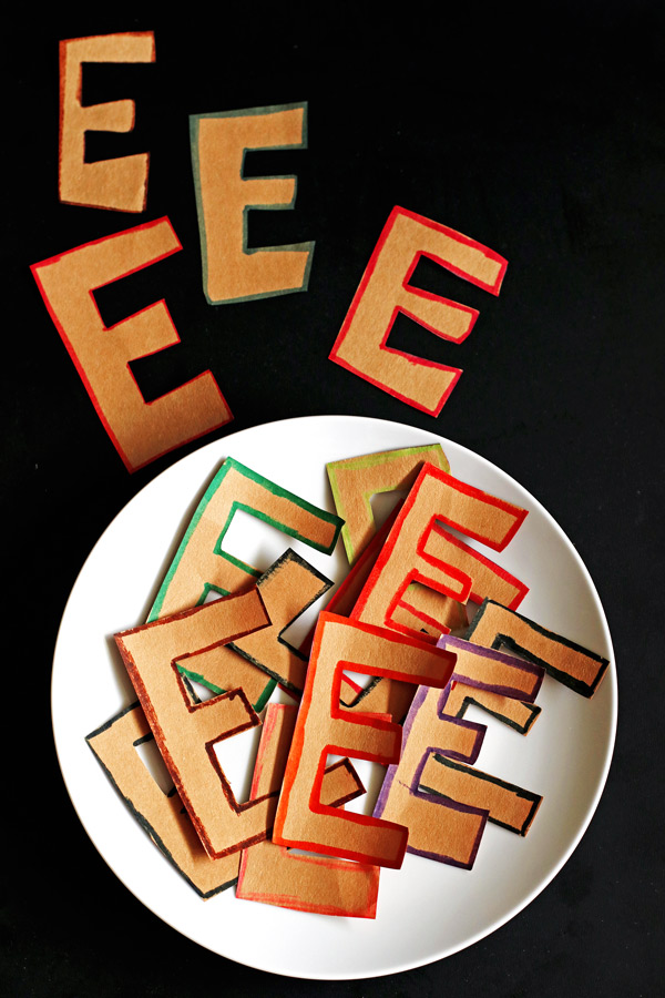 Several capital letter E's cut out from brown paper on a white plate. They are part of an April Fools Day joke.