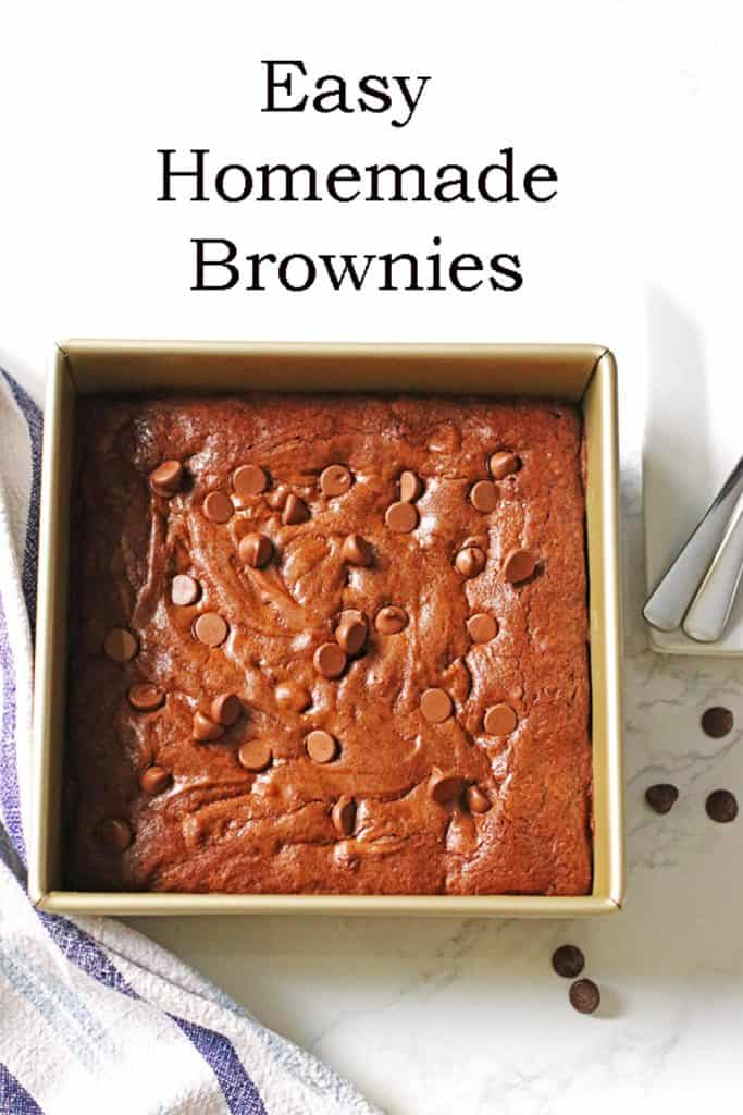 Homemade Brownies with chocolate chips on top in a square baking pan with white plates and spoons next to the pan