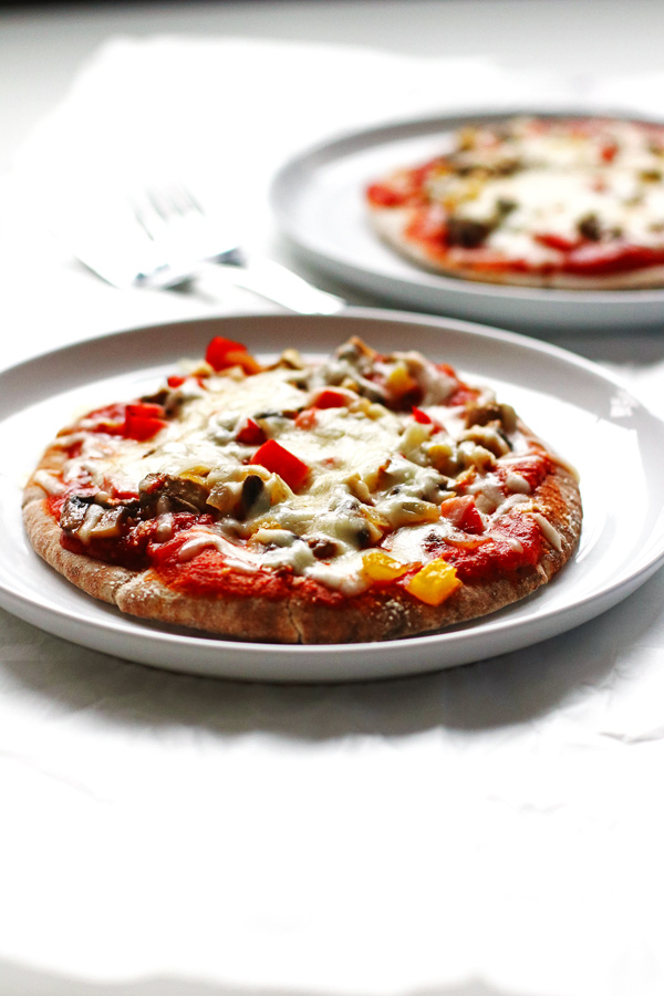This recipe for Veggie Pita Pizzas are made on whole wheat pitas and covered with peppers, onions, mushrooms and cheese.