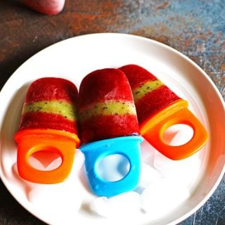 Strawberry Kiwi Popsicles on a white plate sitting on a multi-colored counter