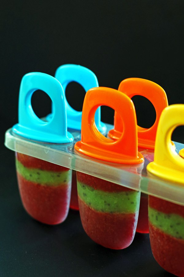 Popscile molds filled with strawberry, kiwi and strawberry puree