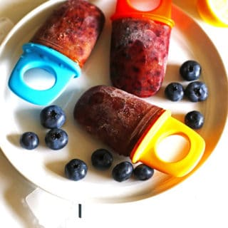 Homemade healthy popsicles on a white plate with blueberries.