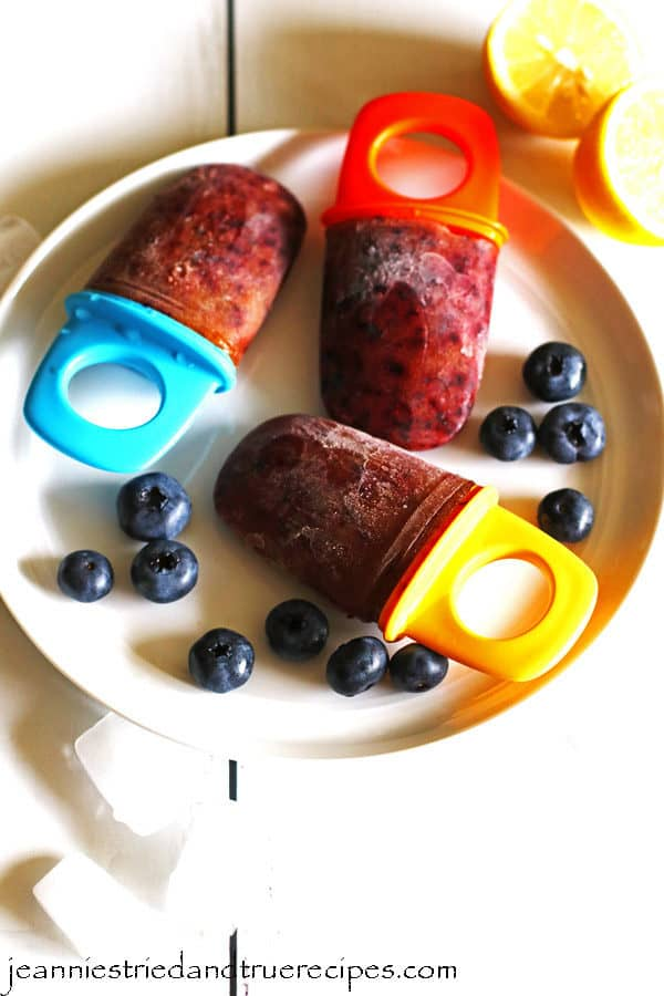 Homemade healthy popsicles on a white plate with some blueberries on the plate.