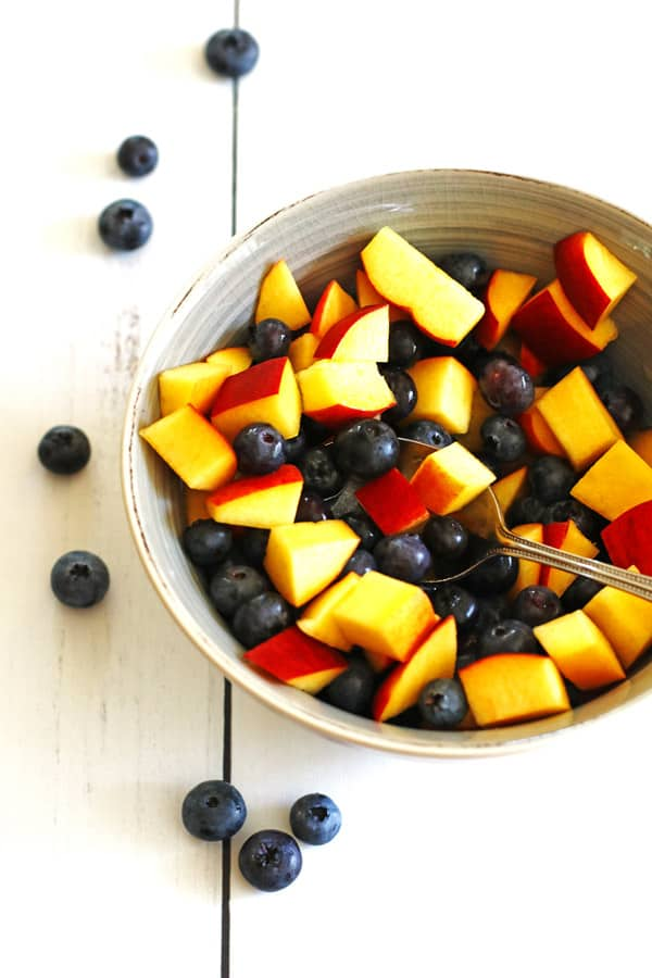 Blueberries and sliced peaches in a grey bowl.