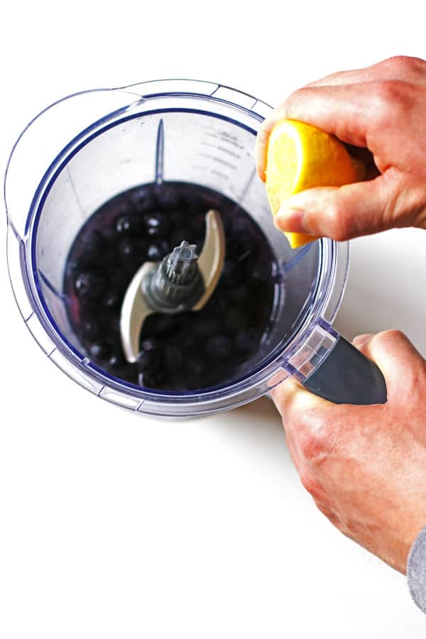 Blueberries and water in blender and squeezing a lemon over the blender