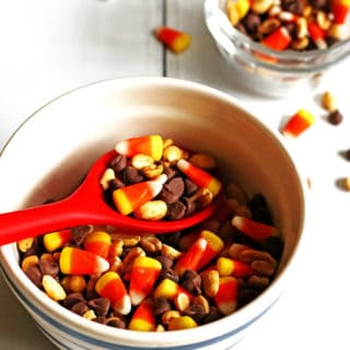 Candy Corn Snack Mix in a bowl with a red spoon scooping it out.
