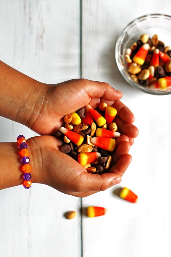 Candy Corn Snack Mix in a kids hands with a small bowl of the mix next to her hands