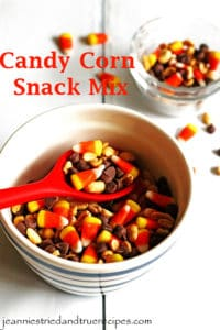 Candy Corn Snack Mix in a bowl with the snack being served with a red spoon. There is a small dish with the snack in it.