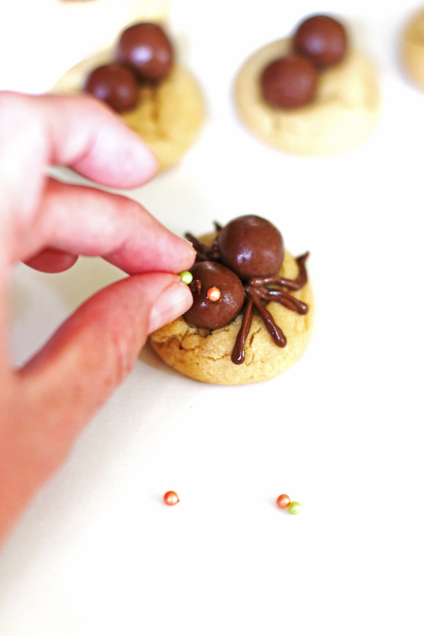 Placing the candy eyes on the spiders that are on top of the cookies.