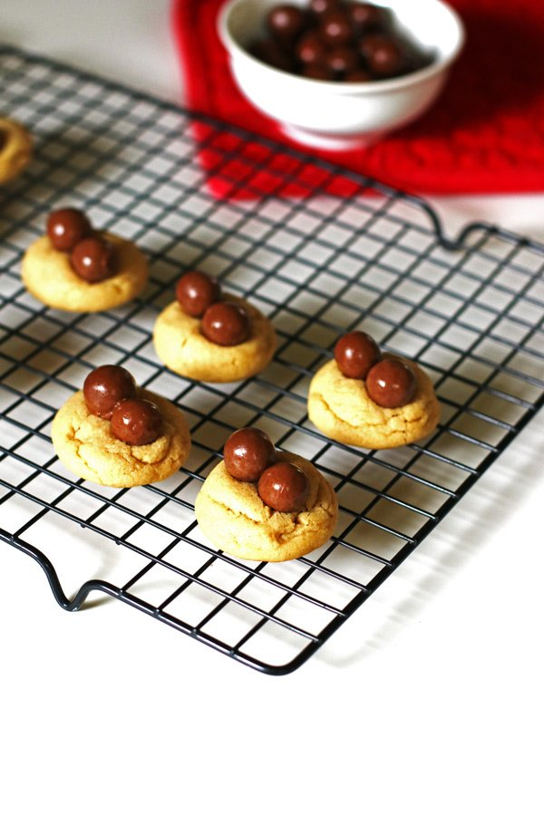 Peanut butter cookies with Whopper candy on cooling rack