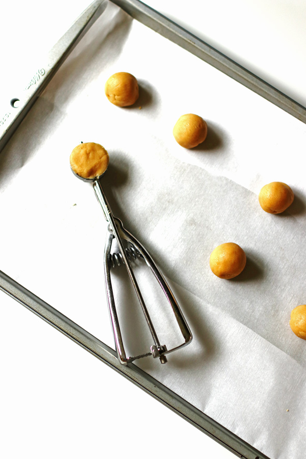 Peanut butter dough balls on baking sheet covered with parchment paper