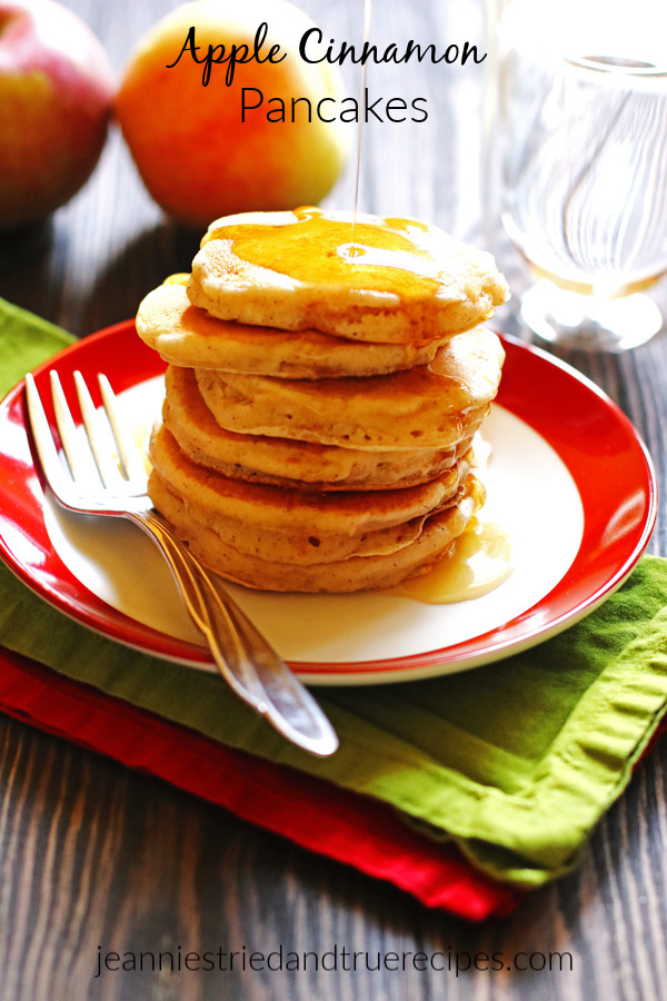 Apple Cinnamon Pancakes stacked on a plate and drizzled with syrup