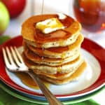 A stack of Apple Pancakes on a plate. There is sliced butter and maple syrup on the pancakes.