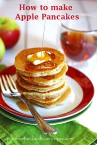 A stack of Apple Pancakes on a red and white plate. There is a slice of butter on top of the pancakes and syrup being poured over them.