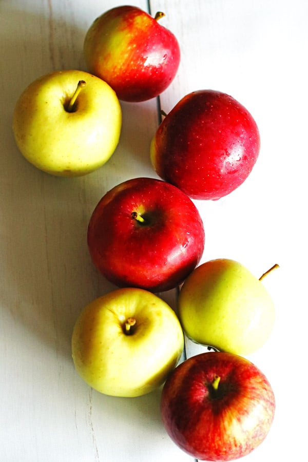 Red and green apples on a white table