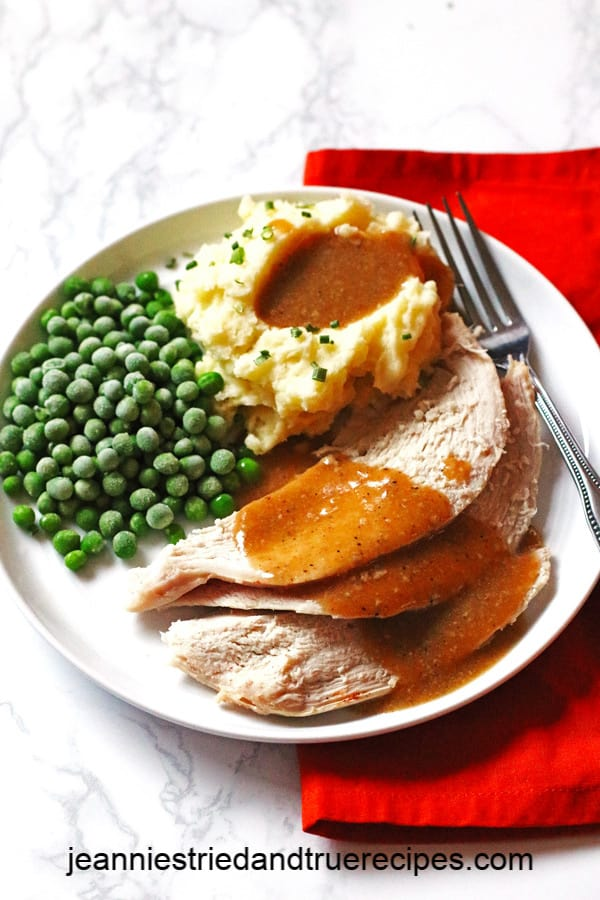 Sliced turkey with gravy, mashed potatoes and peas on a white plate with a fork