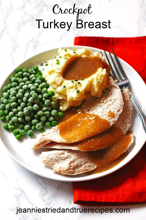 Turkey, homemade gravy, mashed potatoes and peas on a white plate with a fork