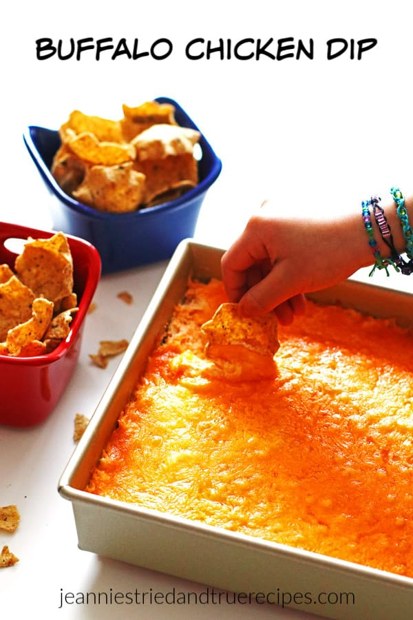 Someone scooping Buffalo Chicken Dip in a pan with a tortilla chip