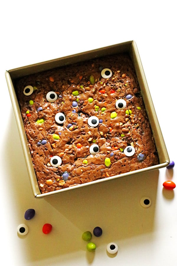 Brownies in a square pan with crushed up candy and edible eyes on top