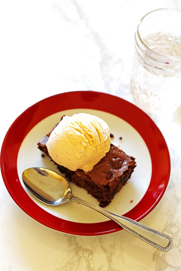 Brownie on a red and white plate with a scoop of vanilla ice cream on top of the brownie