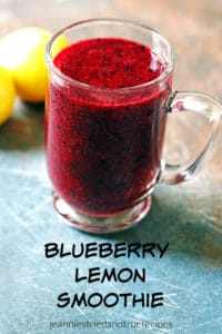 Blueberry Smoothie in a glass mug with a sliced lemon next to it