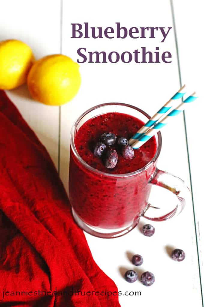 Blueberry Smoothie in a clear mug with a few frozen berries on top. Lemons and blueberries are on the table near the smoothie.
