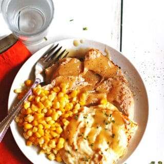 Sliced turkey with gravy, mashed potatoes and corn on a white plate with a fork
