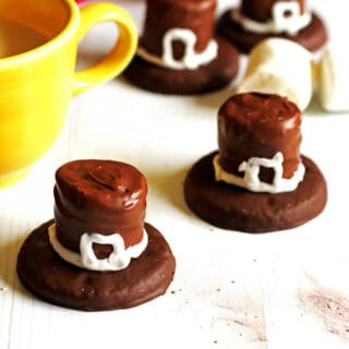 Cookies that are decorated as Pilgrim Hats sitting on a white table with a glass of milk