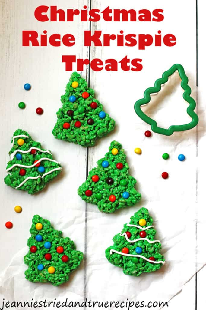 Rice Krispie Treats in the shape of Christmas trees. They are decorated with M&M candy and white icing.
