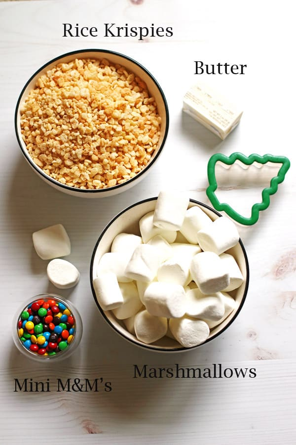 A bowl of rice krispie cereal, a bowl of marshmallows, a small dish with mini M&M candy and a stick of butter along with a tree cookie cutter on a table.
