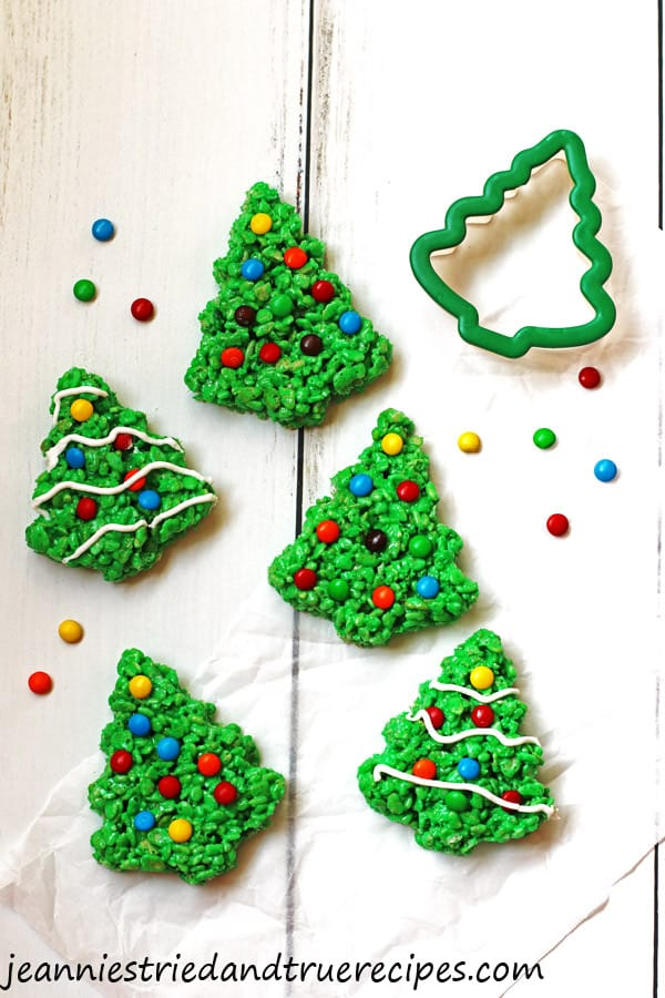 Green Rice Krispie Trees decorated with M&M candy and white icing.