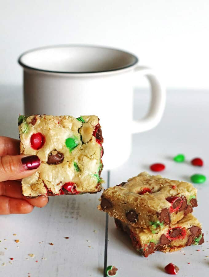 Cookie Bars on table next to a white mug