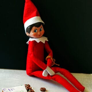 Elf on the shelf sitting with elf donuts