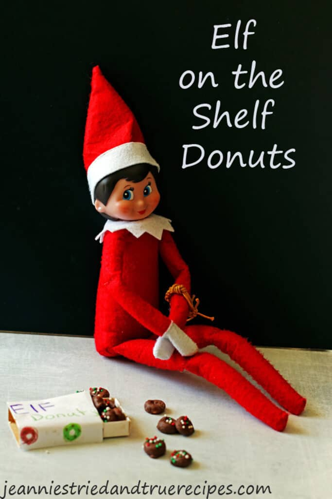 Elf on the shelf sitting next to a box of elf donuts