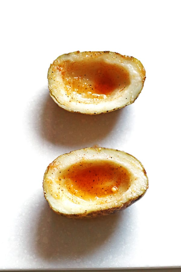 Potato skins cut in half, scooped out and covered with seasoning mixture.
