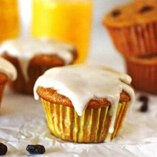 Carrot Cake Muffins on a white table with orange juice in a glass