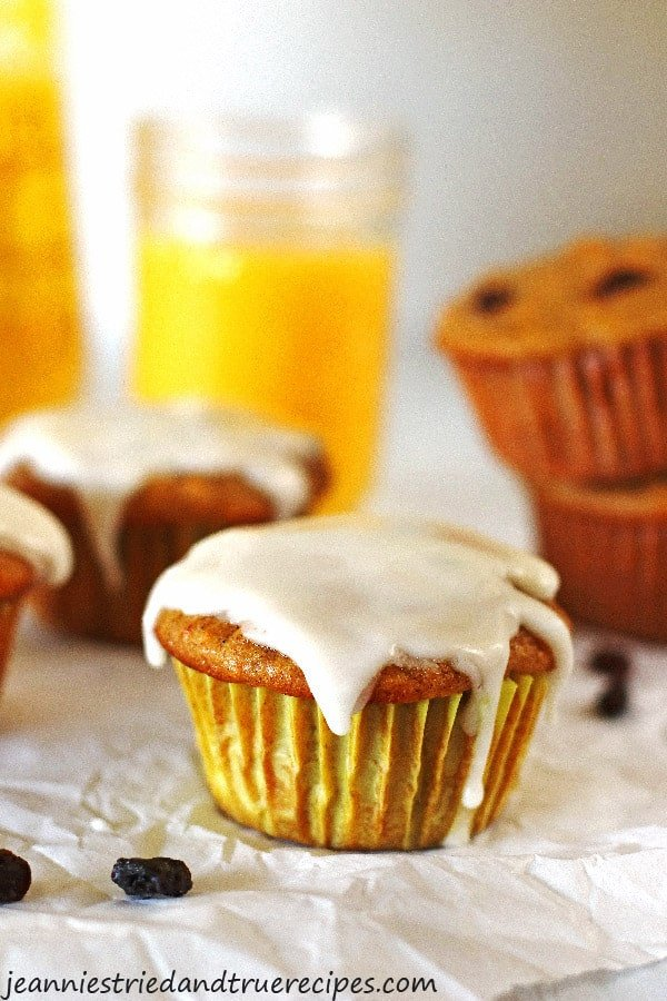 Muffins on a white table with a glass of orange juice