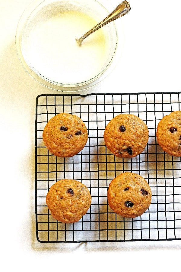 Muffins on a cooling rack with the glaze in a bowl next to them