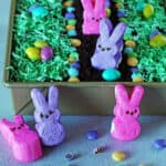 Dirt Cake decorated with bunny Peeps, candy eggs and coconut colored green for grass