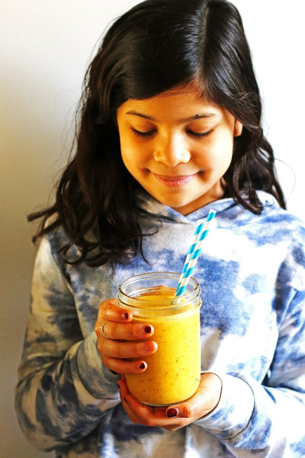 Girl holding smoothie in a canning jar