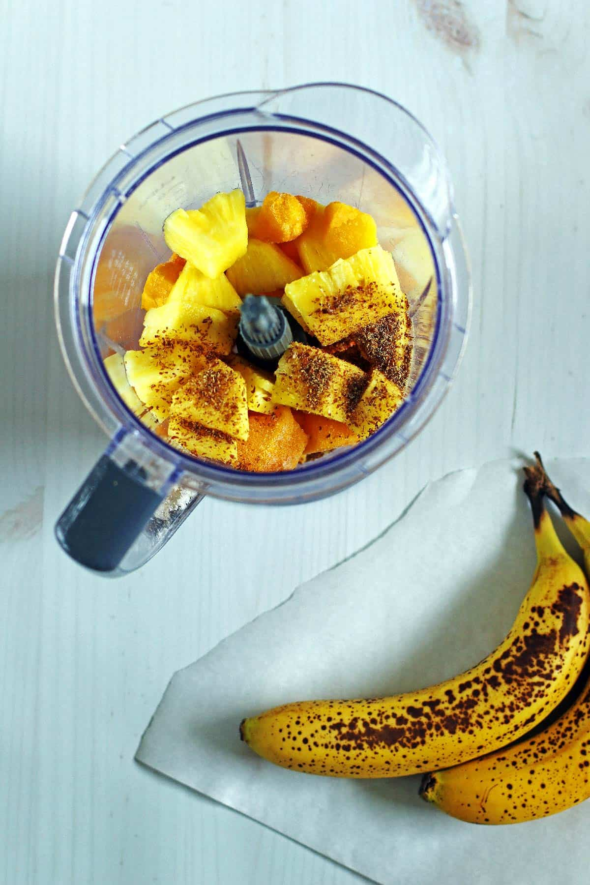 Smoothie ingredients in a blender and bananas next to the blender